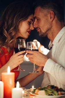 Die junge dame küsst ihren wunderschönen mann beim romantischen abendessen