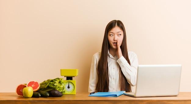 Die junge ernährungswissenschaftlerfrau, die mit ihrem laptop arbeitet, sagt geheime heiße bremsennachrichten und schaut beiseite
