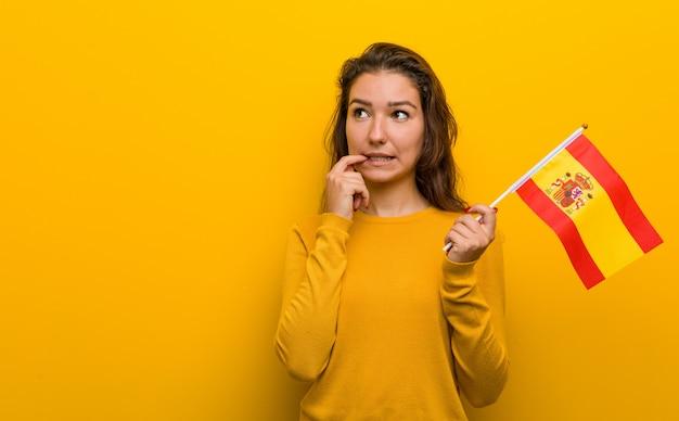 Die junge europäische frau, die eine spanische flagge hält, entspannte sich das denken an etwas, das einen kopienraum betrachtet.