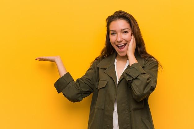 Die junge europäische frau, die über gelb getrennt wird, hält exemplarplatz auf einer palme, unterhalt überreichen backe. erstaunt und entzückt.