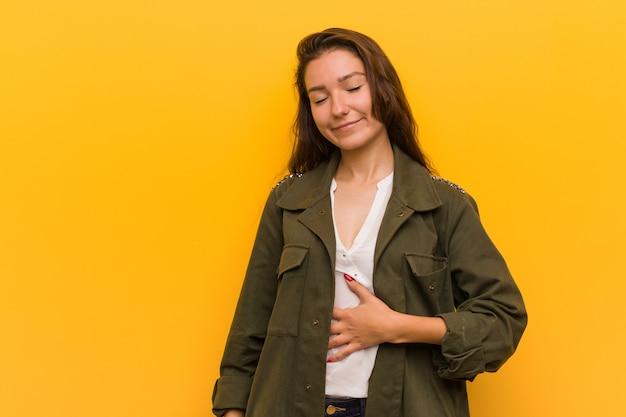 Die junge europäische frau, die über gelb lokalisiert wird, berührt bauch, lächelt leicht und isst und zufriedenheit.