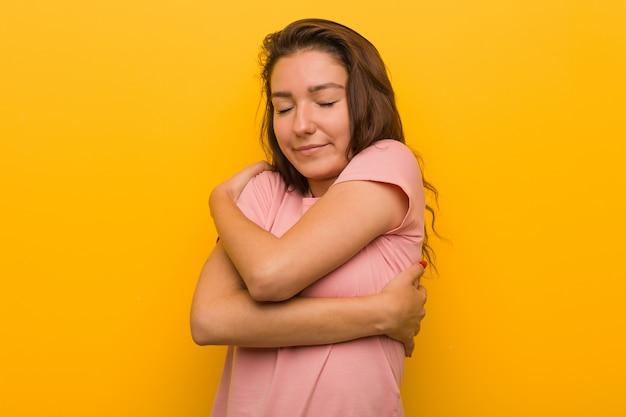 Die junge europäische frau, die über gelb lokalisiert wird, umarmt sich und lächelt sorglos und glücklich.