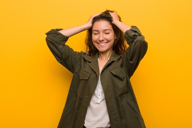 Die junge europäische frau, die über gelbem hintergrund lokalisiert wird, lacht, hände auf kopf froh halten