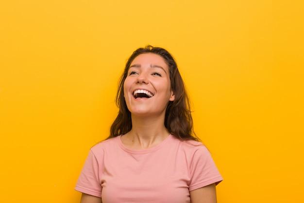 Die junge europäische frau, die über gelbem hintergrund lokalisiert wurde, entspannte sich und das glückliche lachen, der ausgedehnte hals, der zähne zeigt.