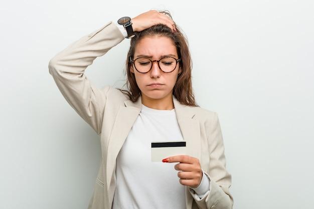 Die junge europäische geschäftsfrau, die eine kreditkarte entsetzt hält, hat sich an wichtige sitzung erinnert.