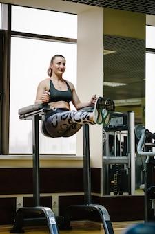 Die junge fitnessfrau, die hängt und mit den bauchmuskeln arbeitet, drückt auf die horizontale stange und hebt seine beine im fitnessclub an