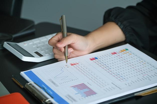 Die junge frau arbeitet und überprüft das budget in ihrer firma