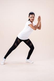 Die junge frau beim zumba-tanztraining klatscht mit der hand und zeigt mit dem zehen nach unten.