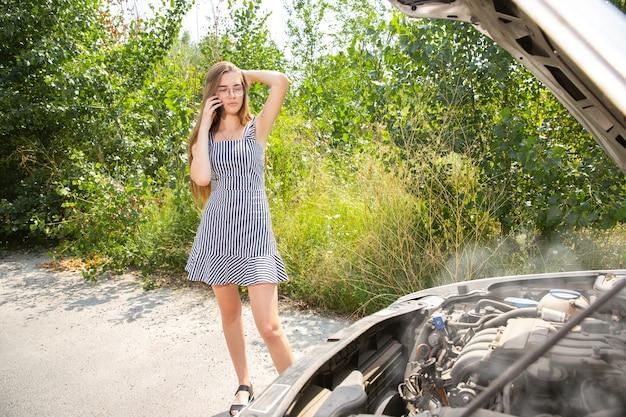 Die junge frau brach auf dem weg zur ruhe das auto zusammen. sie versucht, das kaputte selbst zu reparieren oder sollte per anhalter fahren. nervös werden. wochenende, probleme auf der straße, urlaub.