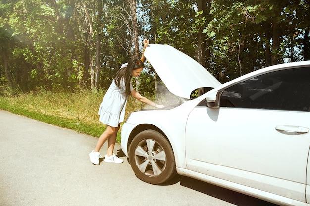 Die junge frau brach auf dem weg zur ruhe das auto zusammen. sie versucht, das kaputte selbst zu reparieren oder sollte per anhalter fahren. nervös werden