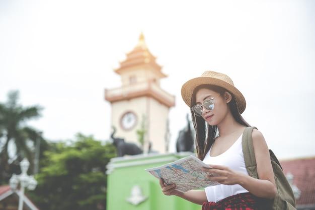 Die junge frau der reisenden mit dem rucksack, der schaut, halten eine karte an der hauptstadt. tourismus tag.