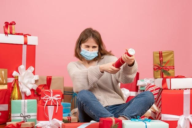 Die junge frau der vorderansicht in der maske, die um weihnachten sitzt, präsentiert blasenden kracher