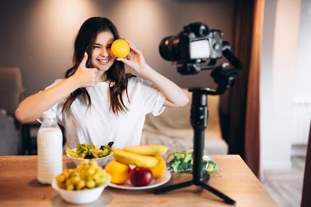 Die junge frau des lebensmittelbloggers kocht frischen veganen obstsalat im küchenstudio und filmt tutorial vor der kamera für videokanal. weibliche influencerin hält orange und spricht über gesunde ernährung.