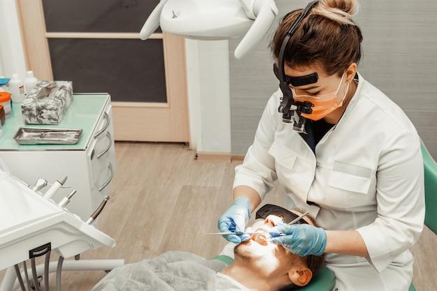 Die junge frau des zahnarztes behandelt einen patienten einen mann. der arzt benutzt einweghandschuhe, eine maske und einen hut. der zahnarzt arbeitet im mund des patienten, verwendet ein professionelles werkzeug.
