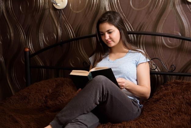Die junge frau, die auf dem bett sitzt und ein buch liest, genießt vom rest ist