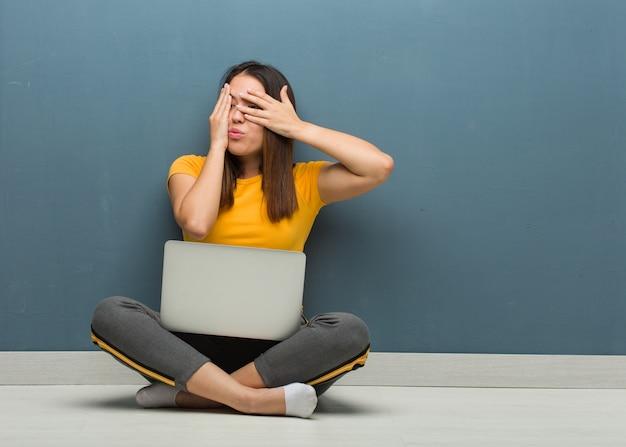 Die junge frau, die auf dem boden mit einem laptop sitzt, fühlt sich besorgt und erschrocken