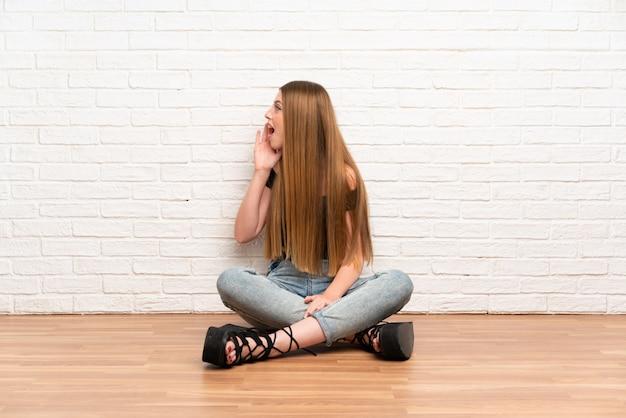 Die junge frau, die auf dem boden schreit mit dem breiten mund sitzt, öffnen sich