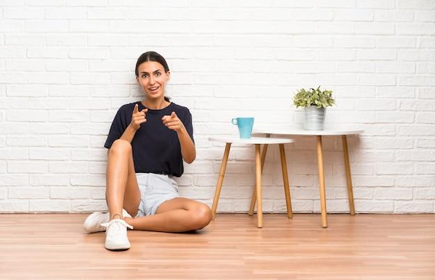 Die junge frau, die auf dem boden sitzt, zeigt finger auf sie