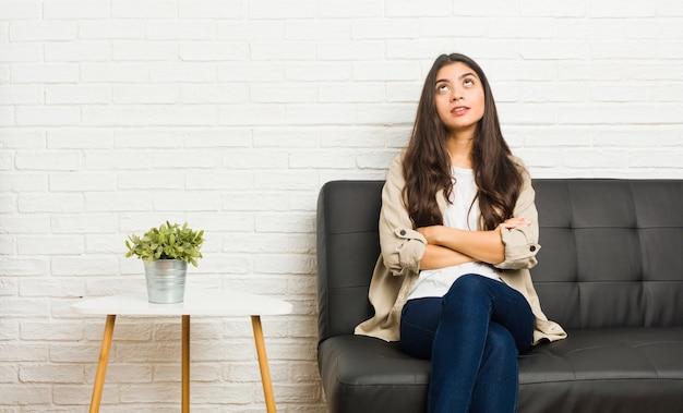 Die junge frau, die auf dem sofa sitzt, ermüdete von einer sich wiederholenden aufgabe