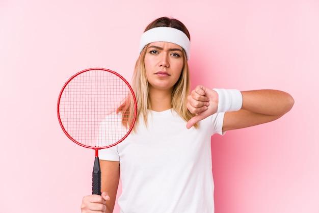 Die junge frau, die badminton spielt, lokalisierte das zeigen einer abneigungsgeste, daumen unten. uneinigkeit konzept.