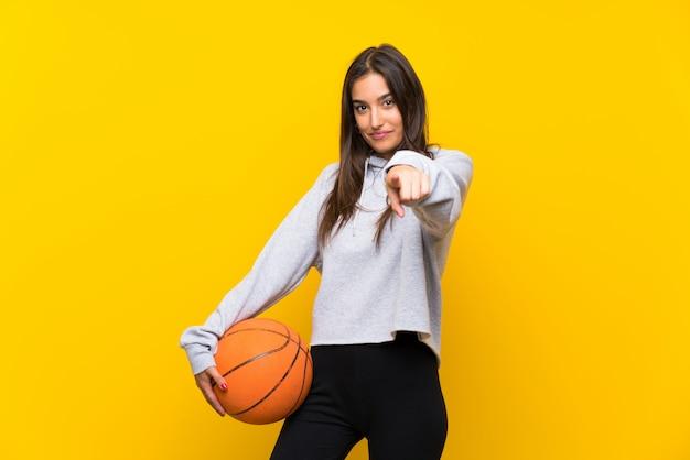 Die junge frau, die basketball über lokalisierter gelber wand spielt, zeigt finger auf sie mit einem überzeugten ausdruck