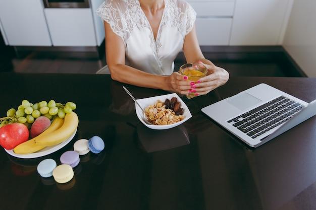 Die junge frau, die beim frühstück mit müsli und milch mit laptop arbeitet