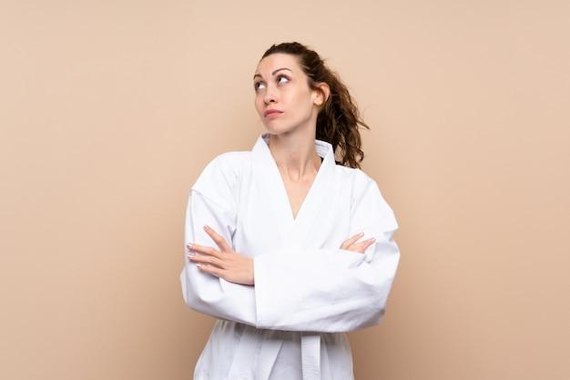 Die junge frau, die das karate macht zweifel macht, gestikulieren beim anheben der schultern