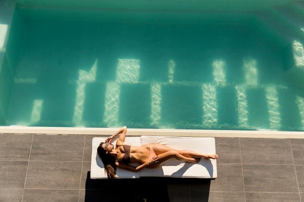 Die junge frau, die durch das pool an liegt, sunbed an ot sommertag