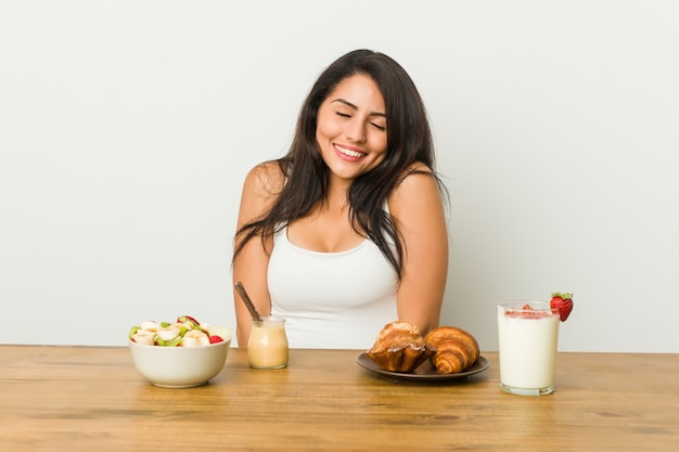 Die junge frau, die ein frühstück nimmt, lacht und schließt die augen, fühlt sich entspannt und glücklich.