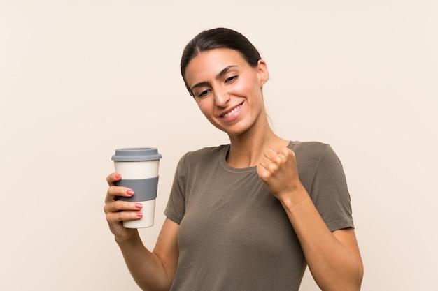 Die junge frau, die ein hält, nehmen den kaffee weg, der einen sieg feiert