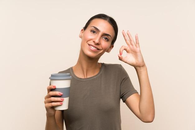 Die junge frau, die ein hält, nehmen den kaffee weg, der okayzeichen mit den fingern zeigt