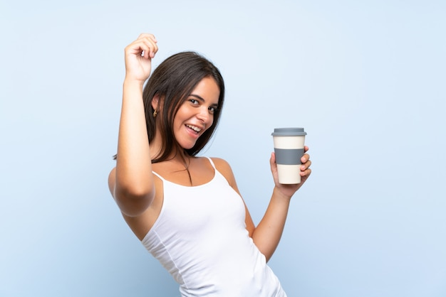 Die junge frau, die ein hält, nehmen kaffee über der lokalisierten blauen wand weg, die einen sieg feiert