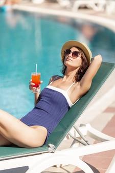 Die junge frau, die ein sitzt, sunbed ein cocktail auf der bank des pools