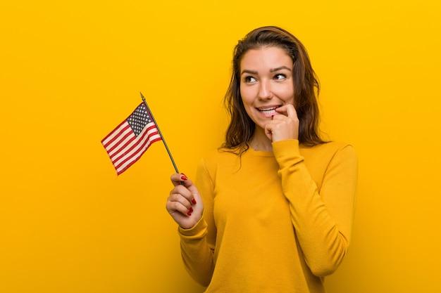 Die junge frau, die eine flagge vereinigter staaten hält, entspannte sich das denken an etwas, das eine kopie betrachtet.