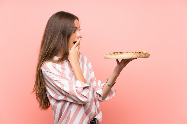 Die junge frau, die eine pizza hält, lokalisierte rosa wand