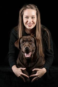 Die junge frau, die einen mischungszuchthund umarmt