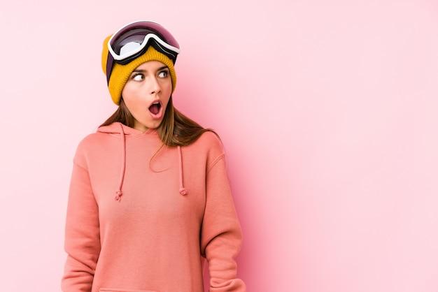 Die junge frau, die einen ski trägt, kleidet das getrennte sein entsetzt wegen etwas, das sie gesehen hat.