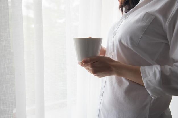 Die junge frau, die einen tasse kaffee auf vorhangfenster hält, masern hintergrund.