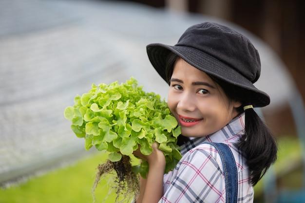 Die junge frau, die grünen kopfsalat im kinderzimmer erntet.