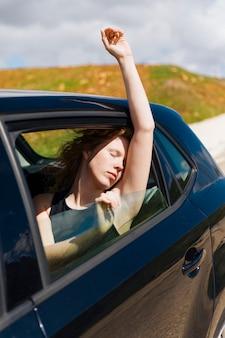Die junge frau, die im auto mit augen sitzt, schloss