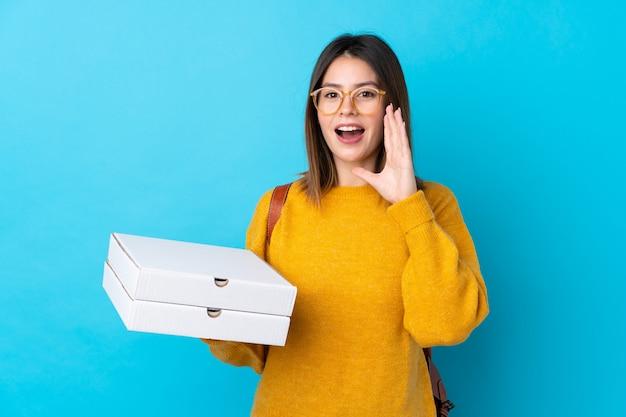 Die junge frau, die kästen einer pizza über lokalisierter blauer wand hält