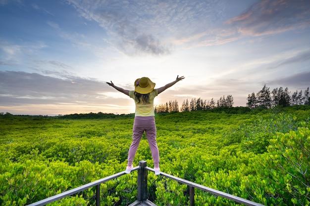 Die junge frau, die mit händen glücklich ist, steigen oben auf schöner mangrovenwaldlandschaft mit schönem