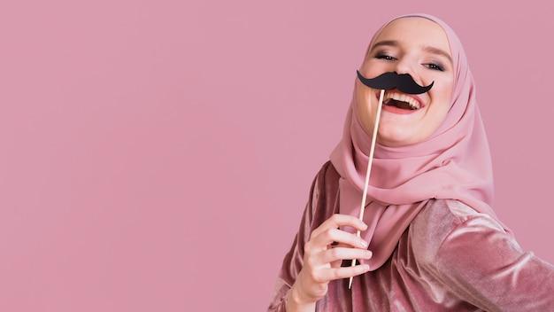 Die junge frau, die papierpartei hält, haftet auf einem rosa hintergrund