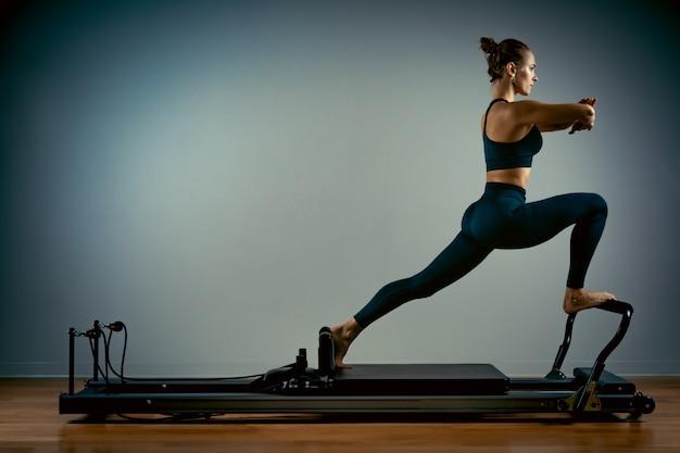 Die junge frau, die pilates tut, trainiert mit einem reformerbett. schöner schlanker fitnesstrainer