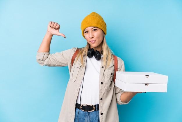Die junge frau, die pizzen hält, fühlt sich stolz und selbstbewusst