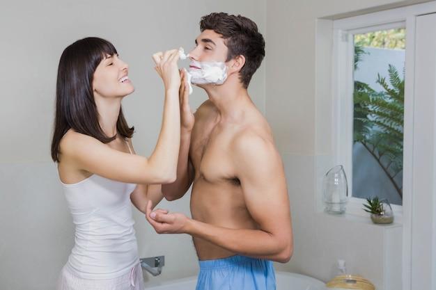Die junge frau, die rasierschaum auf jungen aufträgt, bemannt gesicht im badezimmer