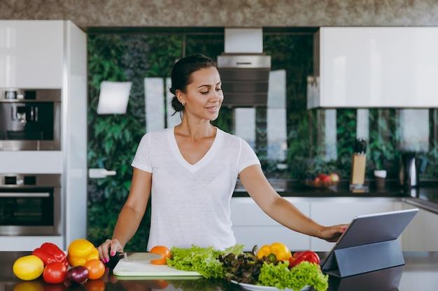 Die junge frau, die rezept im laptop in der küche betrachtet