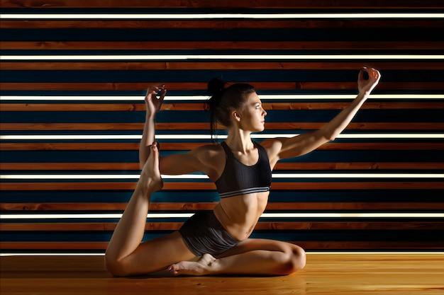 Die junge frau, die yoga tut, trainiert im dunklen studio. gesundheit lifestyle-konzept.