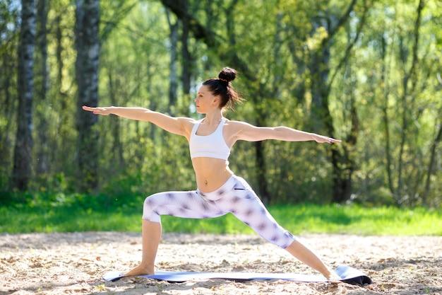 Die junge frau, die yoga tut, trainiert im sommerstadtpark