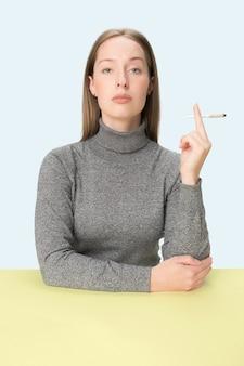 Die junge frau, die zigarette raucht, während sie am tisch an sitzt